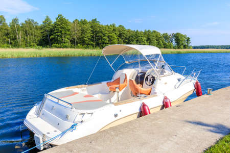 Luxury motorboat anchoring in Pisz sailing port on Lake Ros on summer sunny day, Masurian Lakes, Poland