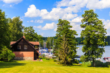 View of Wierzba port buildings with sailing boats on lake Beldany on summer sunny day, Mazury Lake District, Poland