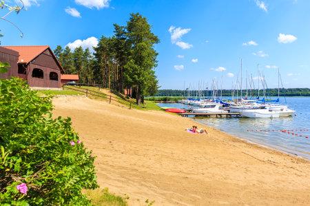 KARWICA BEACH, POLAND - JUN 25, 2020: Couple of people relaxing on beach at lake Nidzkie shore in Krzyze village port on sunny summer day, Mazury Lake District, Poland. Publikacyjne