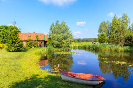 Fishong boat on shore of small pond and old traditional rural house in Galkowo village near Krutynia river, Masurian Lakes, Poland Publikacyjne