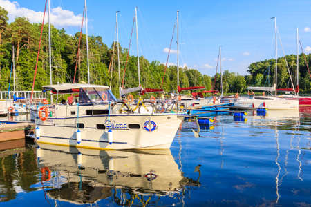 RUCIANE-NIDA PORT, POLAND - JUN 28, 2020: Sailing boats mooring in small port in Ruciane Nida, Masurian Lakes, Poland. Publikacyjne