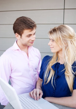 Portrait of a happy young professional couple using laptop standing outside photo