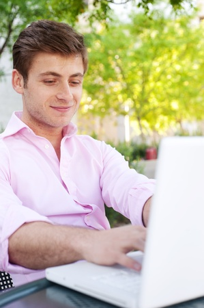 Young professional man on laptop outside photo