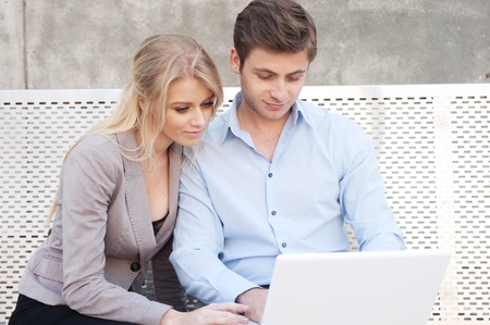 Portrait of a happy young professional couple using laptop sitting outside photo