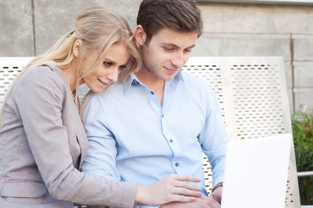 laptop outside: Portrait of a happy young professional couple using laptop sitting outside Stock Photo