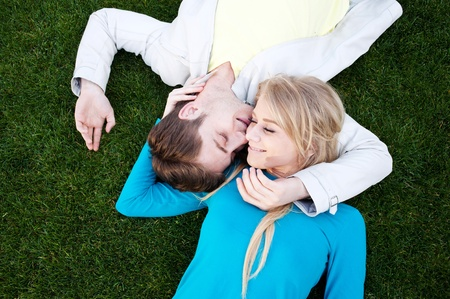 young happy couple in love lying in grass photo