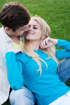 young happy couple in love sitting in grass Stock Photo