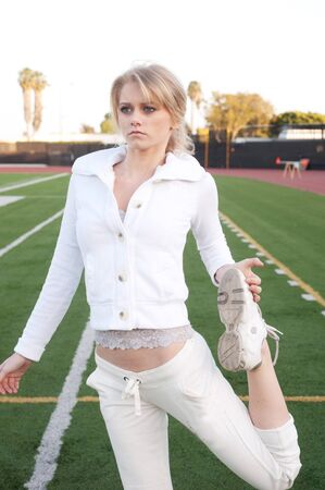 athletic wear: young woman wearing white athletic wear stretching on athletic field