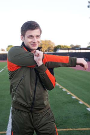 jonge man een warming up en stretching op sportveld