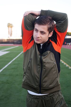 young man warming up and stretching on athletic field photo