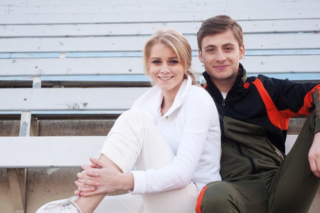 happy male and female athletes sitting in the bleachers photo