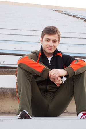 handsome male athlete sitting in the bleachers photo