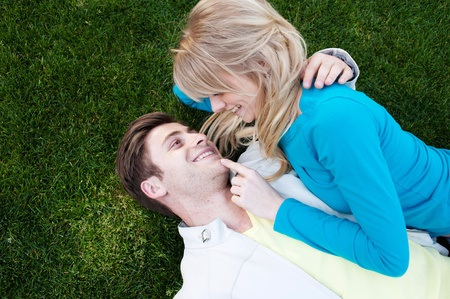 portrait of a happy young couple together in love lying in grass photo