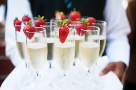 champagne glasses: Waiter serving champagne on a tray with strawberries Stock Photo
