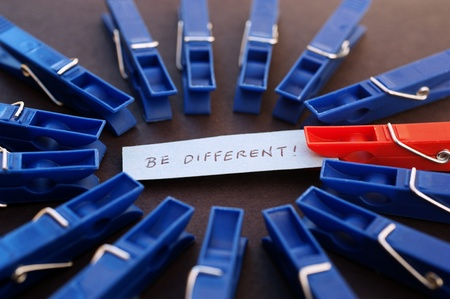 Being different, blue clothespins and one red clothespin Stock Photo - 13101590