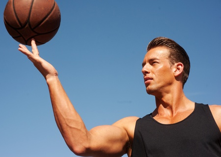 portret van een mannelijke basketbal speler met een bal buiten tegen de blauwe hemel