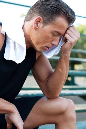 Portrait eines jungen sportlichen Mann mit Workout-Handtuch sitzt auf der Tribüne Standard-Bild - 13101748