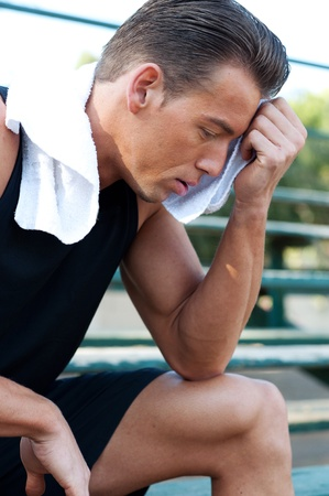 bleachers: Portrait of a young athletic man with workout towel sitting on the bleachers