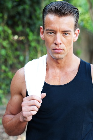 portrait of a young athletic man with workout towel standing outside photo
