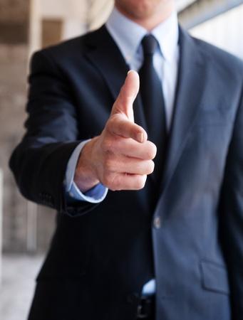buen trato: Hombre de negocios que apunta con un gesto de la mano de pie fuera