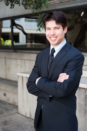 Portrait of a young businessman in suit standing outdoors