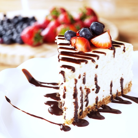Slice of cheesecake topped with strawberries and blueberries on a plate with chocolate syrup
