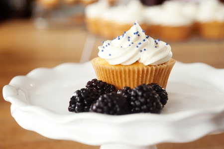 Cupcake on a plate with blackberries resting on a table
