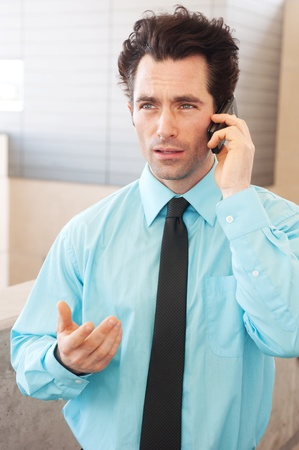 Frustrated executive on cell phone standing outside photo