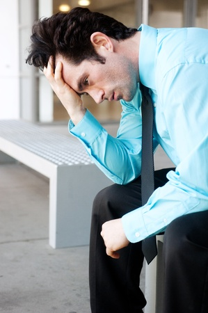 Frustrated businessman sitting on a bench running fingers through hair Stock Photo