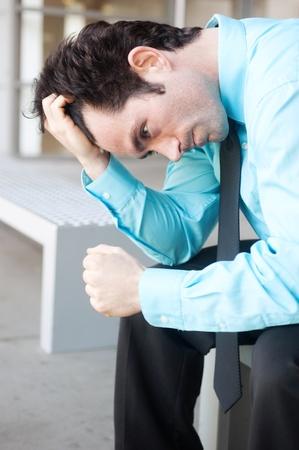 Frustriert Geschäftsmann sitzt auf einer Bank läuft Fingern durch das Haar Standard-Bild - 13138671