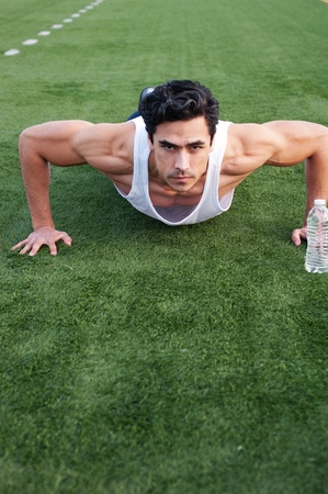 Handsome, young latino athlete doing push ups on an athletic field photo
