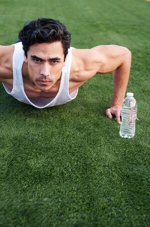 Deportista guapo, joven latino haciendo flexiones en un campo de atletismo Foto de archivo - 13138130