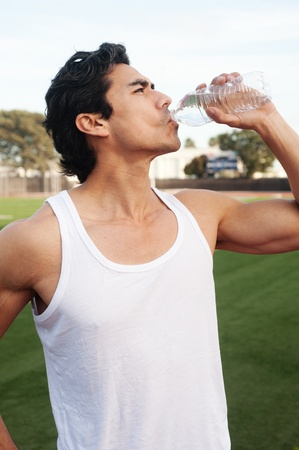 man drinking water: Handsome, young latino athlete drinking water standing on athletic field