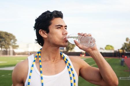Beau, jeune latino de l'eau potable athlète debout sur un terrain de sport Banque d'images