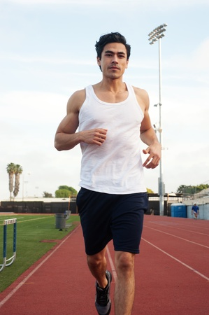 jogging track: handsome, young latino runner on athletic field