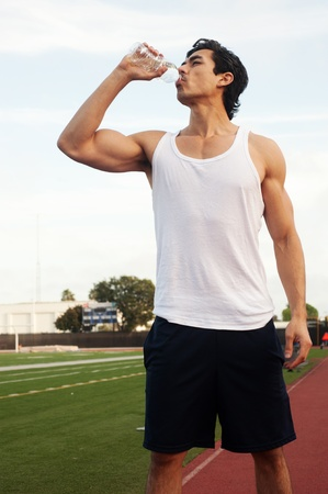 man drinking water: Young male latino athlete drinking water standing on athletic field