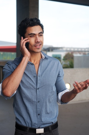 Handsome, young latino businessman on phone standing outside photo