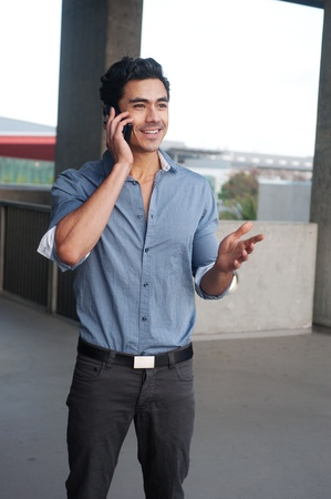 Handsome, young latino businessman on phone standing outside