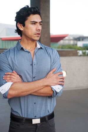 Handsome, young latino professional businessman standing outside photo