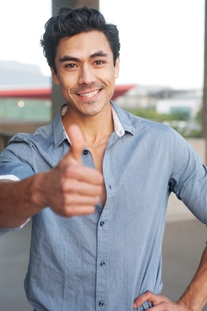 Young, handsome businessman giving thumbs up standing outside  Stock Photo