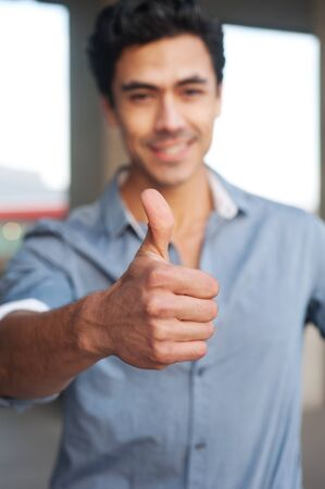 Young, handsome businessman giving thumbs up standing outside  photo