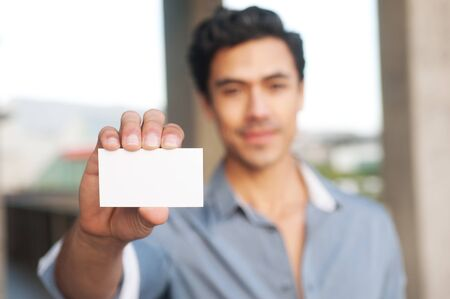 holding close: Young handsome businessman presenting blank business card