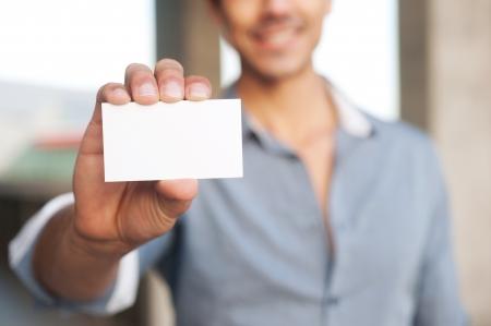 Jonge knappe zakenman presenteren blanco visitekaartje