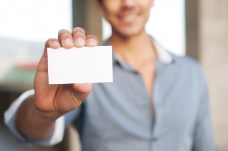 business card in hand: Young handsome businessman presenting blank business card