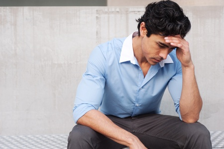 hispanic student: Frustrated young, handsome latino businessman sitting outside