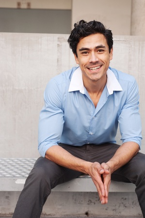 Handsome, young latino businessman sitting outside photo