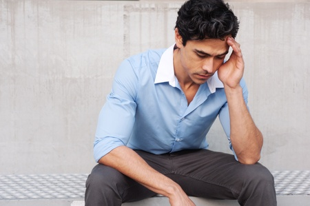 Frustriert junge, hübsche Latino Geschäftsmann sitzt draußen Standard-Bild - 13139259