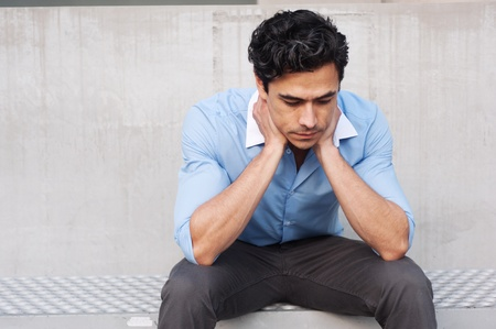 Frustrated young, handsome latino businessman sitting outside