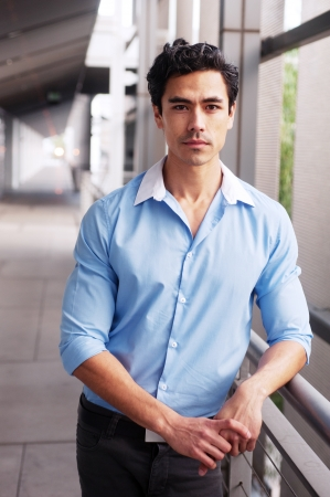 Handsome, young latino businessman standing outside Stock Photo