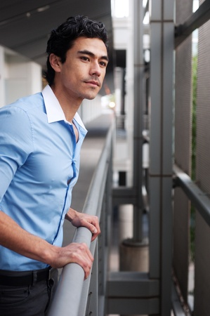 Handsome, young latino businessman standing outside photo